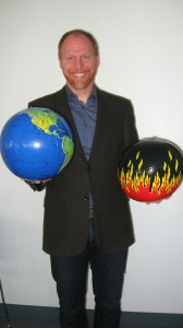 Thomas Doherty holds two visions of the globe at an Antioch New England speaking event in December. (Photo by Hanna Wheeler)