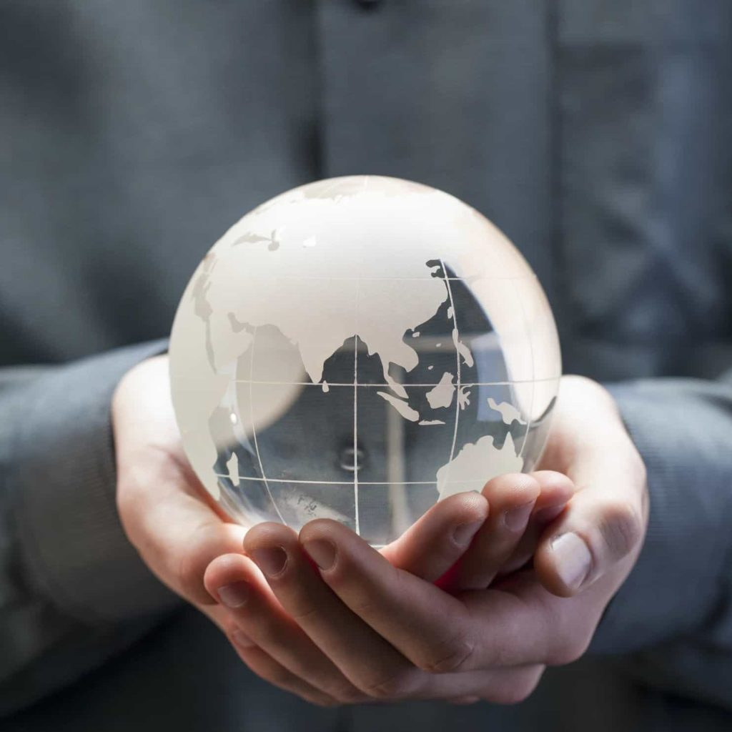 Hands holding a glass globe of the world.